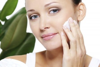 Woman gently putting on natural skin care lotion